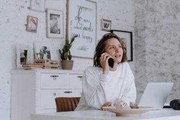 Vrouw belt achter haar bureau.