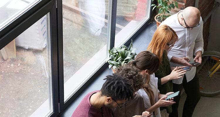 Vijf mensen kijken tegelijkertijd naar hun telefoon