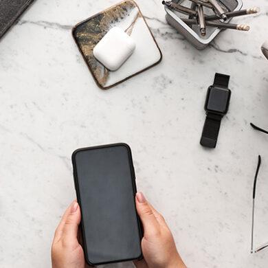 Flatlay met smartwatch, smartpone, koffie en EarPods.