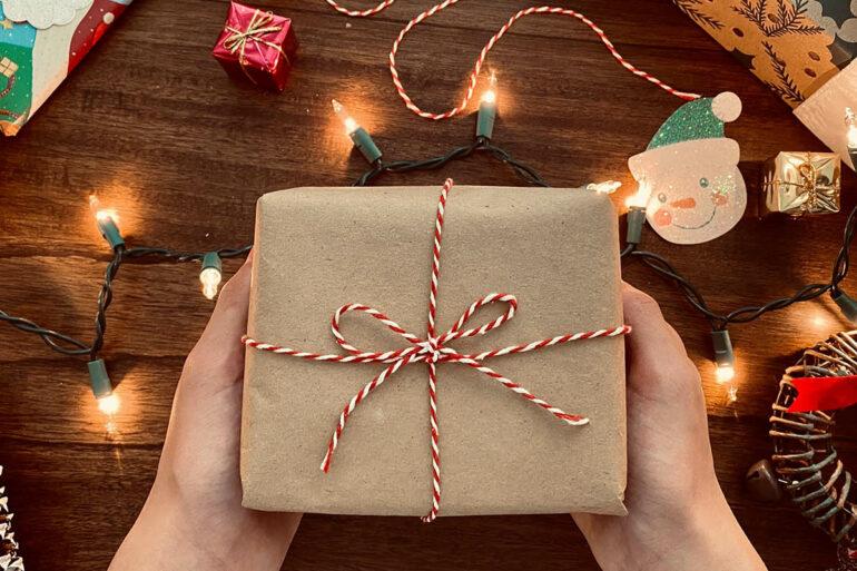 Ingepakt cadeautje met kerstverlichting rondom