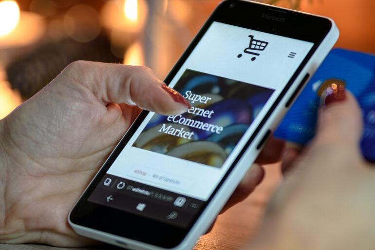 Persoon shopt via haar telefoon met de creditcard bij de hand.