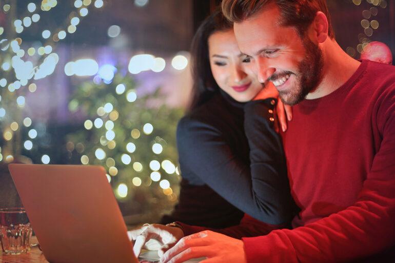 Man en vrouw zoeken cadeaus achter laptop