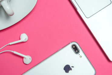 Flatlay van smartphone, laptop, oortjes en kop koffie.