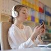 Persoon houdt telefoon vast zittend aan een bureau