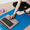 Vrouw volgt sportles via de laptop
