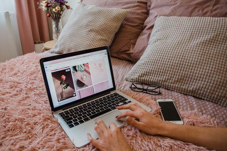 Persoon gebruikt macbook op bed