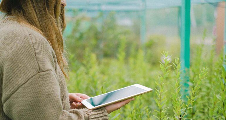 Vrouw met Ipad in tuin