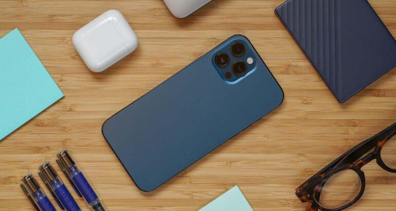 iPhone 12 Pro Max op een bureau omgeven door andere technologie en kantoor elementen